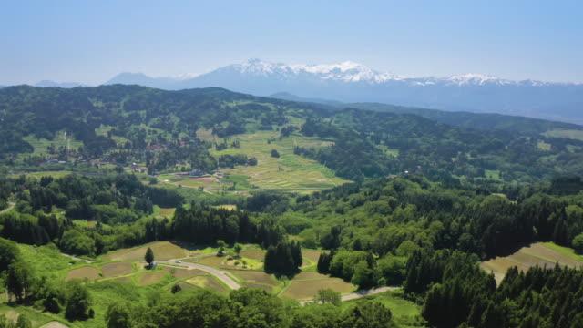 ws aerial landscape with fields and snowcapped mountain range, myoko, niigata prefecture, japan - mountain range点の映像素材/bロール