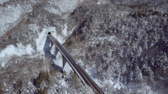 aerial landscape with forest bridge in winter, shiga highlands, joshin etsu-kogen national park, nagano prefecture, japan - joshinetsu kogen national park stock videos and b-roll footage
