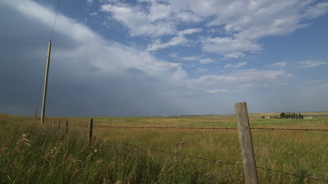landscape with wire fence and telephone pole. - alberta stock videos & royalty-free footage