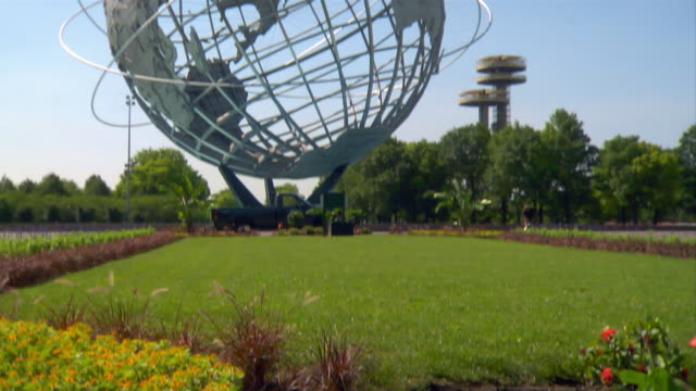 a landscaper grooms the grounds surrounding the unisphere. - flushing meadows corona park stock videos and b-roll footage