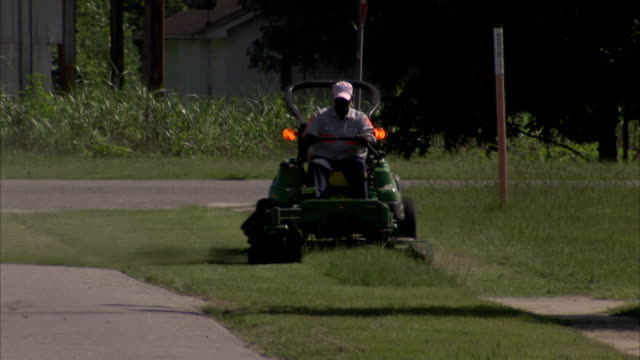 A landscaper mows grass between a city street and sidewalks. Available in HD.