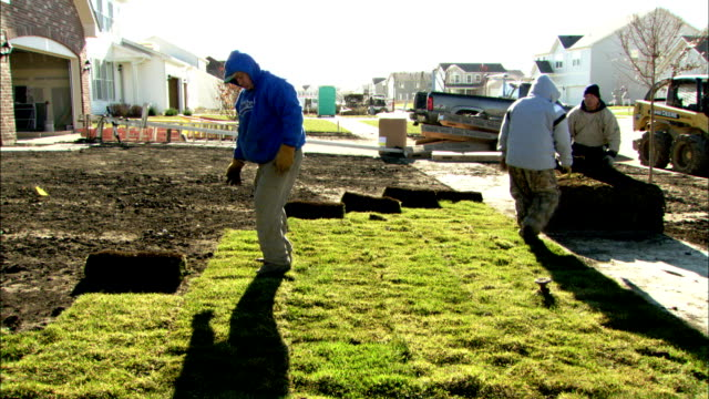 Landscapers roll sod onto the yard of a new house. Available in HD.