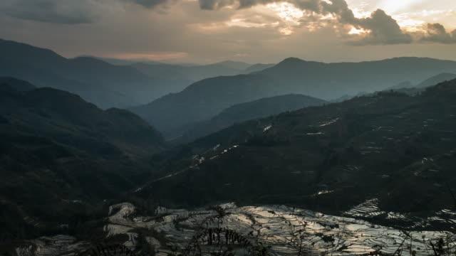 vidéos et rushes de paysages de montagne et le riz terrasse avec rayon de lumière dans la chine - exotisme