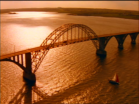 AERIAL Lango Bridge over water with sailboat at sunset / orange filter / Fyn, Denmark