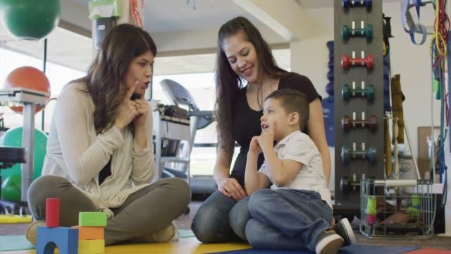language speech pathologist demonstrates a sound to a young hispanic boy - pathologist stock videos and b-roll footage