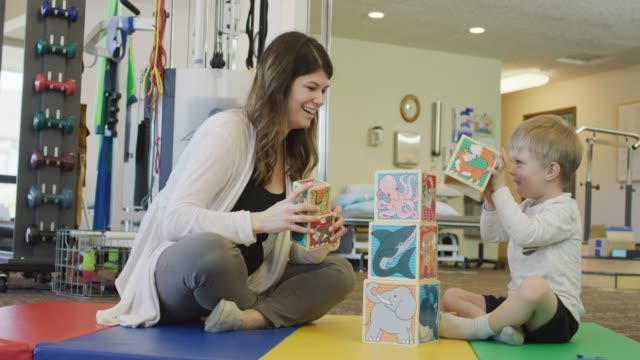 language speech pathologist working with a young boy - pathologist stock videos and b-roll footage