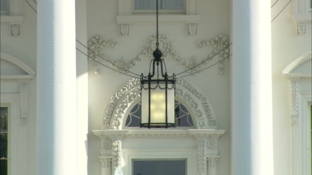 A lantern hangs between two pillars at the White House in Washington, DC.