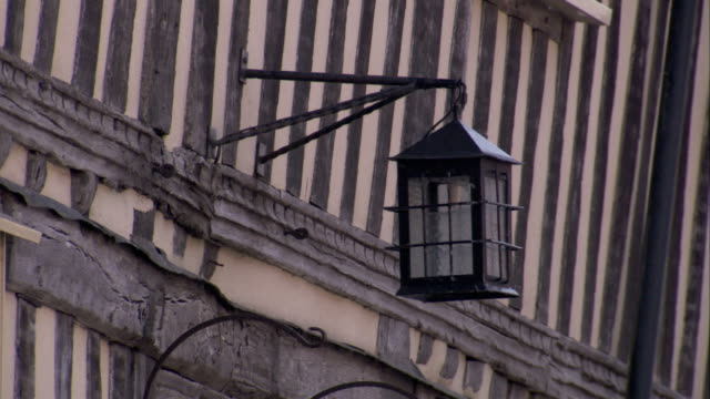 a lantern hangs on the exterior of a medieval cottage in lavenham. available in hd. - lavenham stock-videos und b-roll-filmmaterial