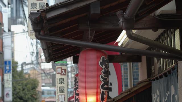 東京のレストランのドアの上に揺れるランタン - 居酒屋点の映像素材/bロール