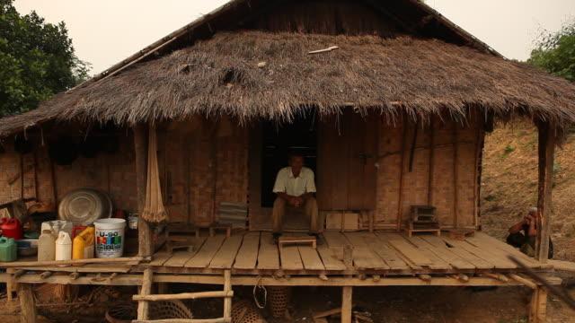vídeos y material grabado en eventos de stock de lao man sits outside wooden home - comunidad global