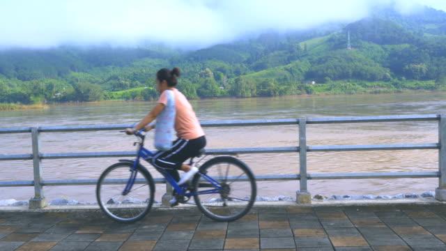 vidéos et rushes de lao / mékong: vélo équitation fille - une seule adolescente