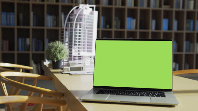 laptop computer with blank green screen on the table over construction project of new building model background. - liquid crystal display stock videos & royalty-free footage