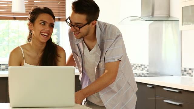 vídeos de stock, filmes e b-roll de laptop casal, cozinha, espaço para texto. - copy space