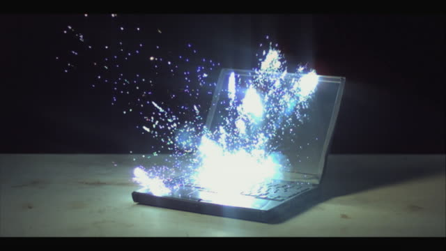 MS SLO MO Laptop exploding with sparks against black background / New Jersey, USA