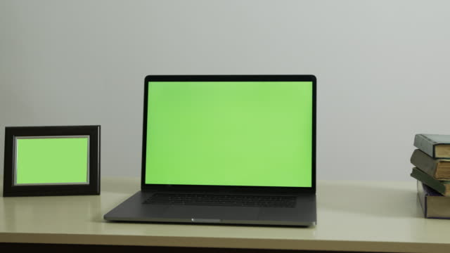 laptop green screen with books and picture frame on green screen - computer monitor white background stock videos & royalty-free footage