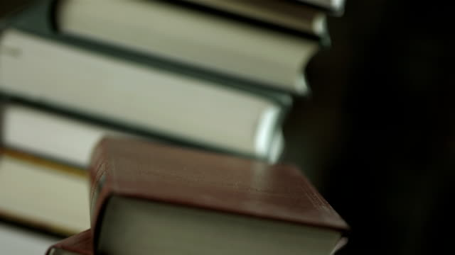 hd: laptop lying on a stack of books - hardcover book stock videos and b-roll footage