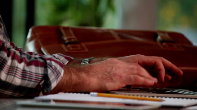 Laptop, man's hands, pencil, briefcase. Close.