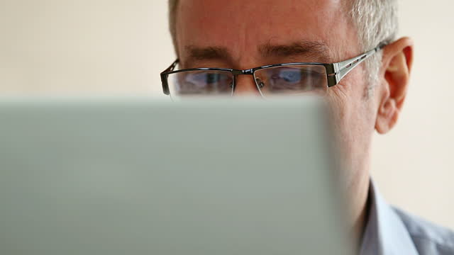 Laptop, mature man with glasses.