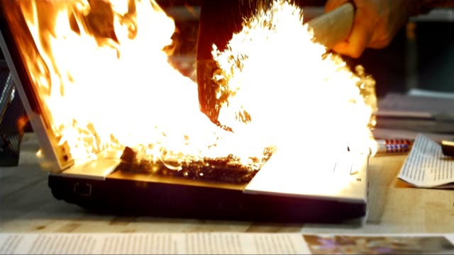 SLO MO Laptop on fire struck by a hammer