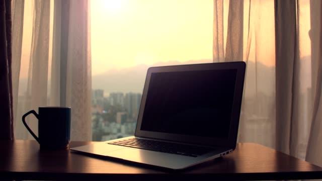 stockvideo's en b-roll-footage met laptop op lijst met rondtrekkende gordijnen - wit scherm