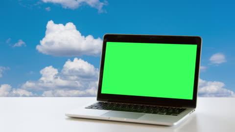 bärbar dator på kontorsbordet över vita moln i blå himmel bakgrund - vid bildbanksvideor och videomaterial från bakom kulisserna