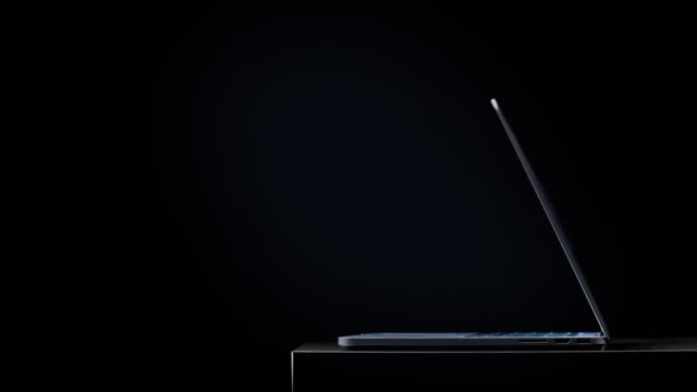 laptop opening with a blue light casting on the keyboard and background from screen - dark stock videos & royalty-free footage