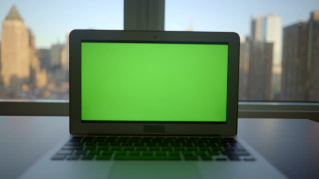 laptop screen isolated with green-screen background. modern high rise office worplace with city skyline view - zoom out stock videos & royalty-free footage