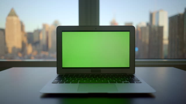 laptop screen isolated with greenscreen background. modern high rise office worplace with city skyline view