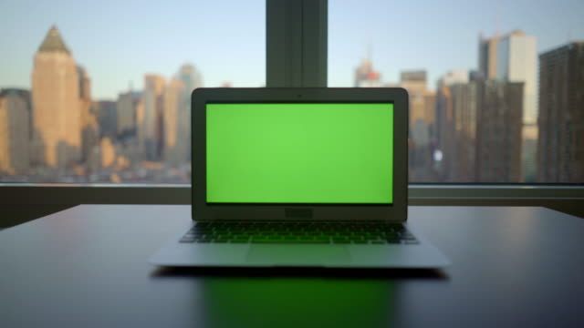 vídeos y material grabado en eventos de stock de laptop screen isolated with greenscreen background. modern high rise office worplace with city skyline view - zoom hacia fuera