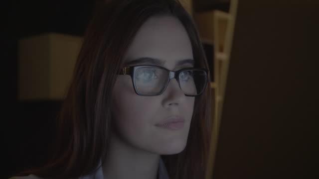 Laptop scrutiny. Young woman glasses.