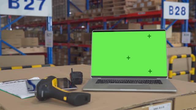 laptop mit green screen-display im lagerraum. ideal für mock-up lieferung und transportkonzept nutzung. - distribution warehouse stock-videos und b-roll-filmmaterial