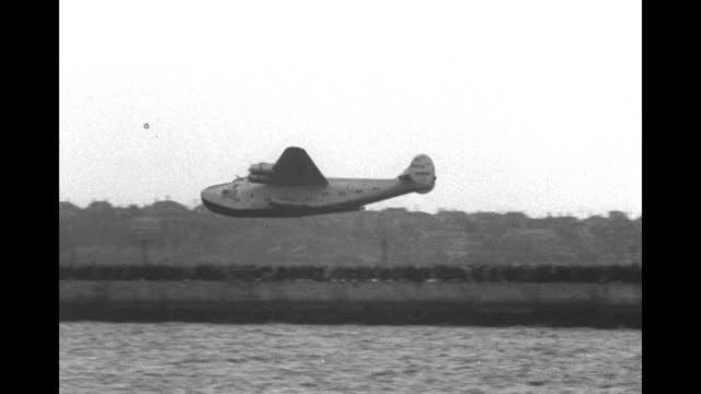 """large airplane comes in for a landing on water as hundreds of people look on / closer view of plane with """"california clipper"""" and pan american... - 水上飛行機点の映像素材/bロール"""
