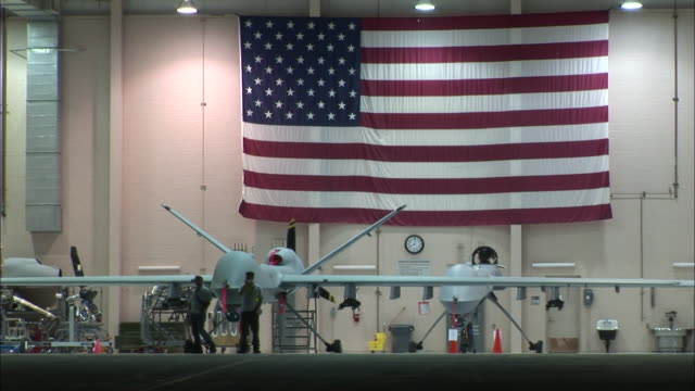 a large american flag hangs on a wall above two predator drones in an airplane hangar. - us military stock videos & royalty-free footage