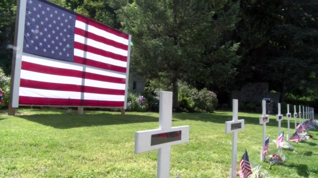vidéos et rushes de large american flag in background with many crosses with small american flags and poppies - salmini