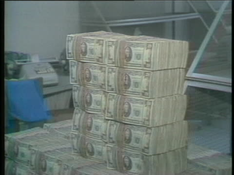 large amount of confiscated drug money sits in neatly packed stacks on a table. - us currency stock videos & royalty-free footage