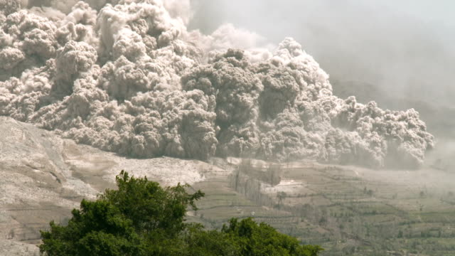 a large and dangerous pyroclastic flow consumes farmland and trees as sinabung volcano in sumatra indonesia erupts on 19th june 2015 - pyroklastischer strom stock-videos und b-roll-filmmaterial