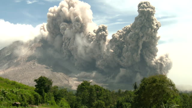 a large and dangerous pyroclastic flow sweeps down the east side of sinabung volcano in sumatra indonesia during a major eruption on 19th june 2015 - pyroklastischer strom stock-videos und b-roll-filmmaterial