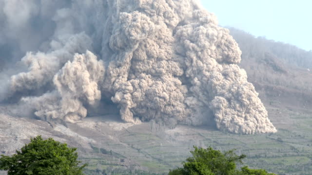 a large and dangerous pyroclastic flow sweeps down the side of sinabung volcano in sumatra indonesia during a major eruption on 19th june 2015 - pyroklastischer strom stock-videos und b-roll-filmmaterial