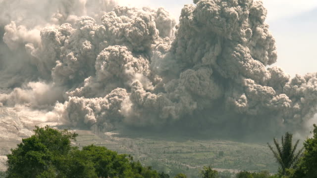a large and destructive pyroclastic flow sweeps over farmland on the flanks of sinabung volcano in sumatra indonesia on 19th june 2015 - pyroklastischer strom stock-videos und b-roll-filmmaterial