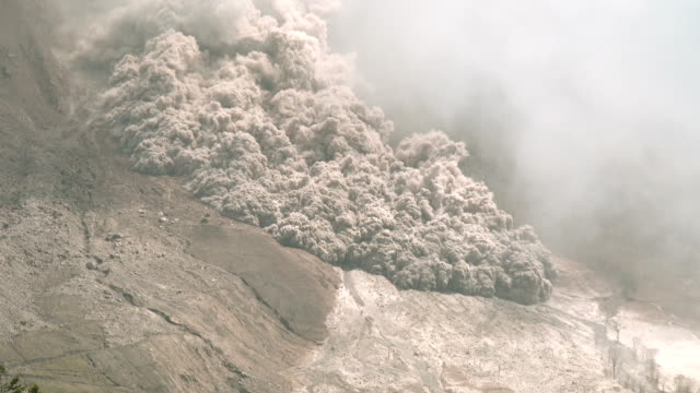 a large and fast moving pyroclastic flow sweeps down sinabung volcano in sumatra indonesia during a major eruption on 19th june 2015 - pyroklastischer strom stock-videos und b-roll-filmmaterial