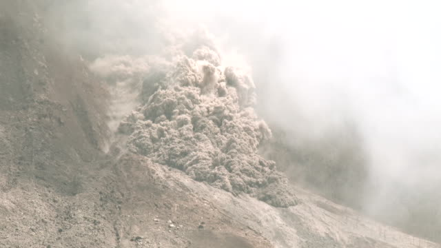 a large and fast moving pyroclastic flow tears down the flanks of sinabung volcano in sumatra indonesia during a major eruption on 19th june 2015 - pyroklastischer strom stock-videos und b-roll-filmmaterial