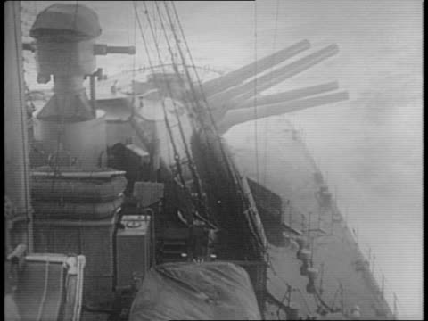 Large artillery cannons lower on the deck of a battleship at sea / a large ship rides over choppy waves on the horizon / a ship's crewman in the...