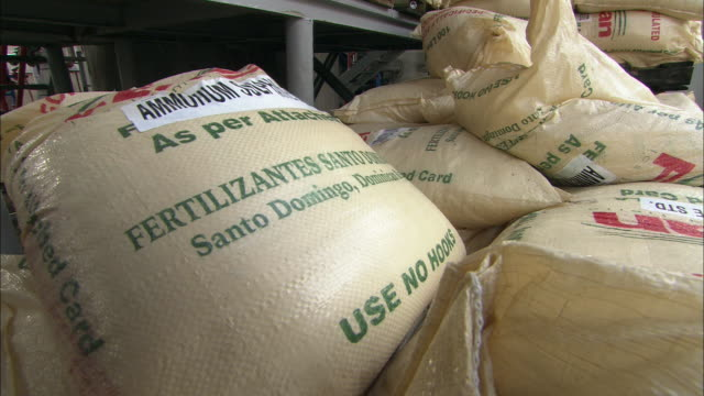 large bags of fertilizer cover the floor and low shelves in a factory. - fertilizer stock videos & royalty-free footage