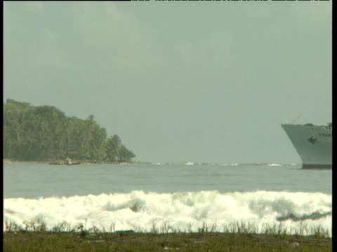 large 'banana boat' container ship slowly enters bay as powerful waves break along shoreline costa rica - 中央アメリカ点の映像素材/bロール