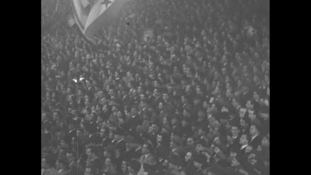 Large banner featuring Franklin Roosevelt Harry Truman Joseph Stalin Clement Attlee flanked by American flags / high angle view of crowd of thousands...