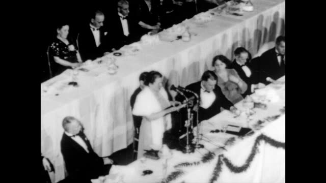 stockvideo's en b-roll-footage met / large banquet hall full of black tie dinner guests / man at podium giving speech / camera pans the many rows of well dressed guests / pearl buck at... - 1938
