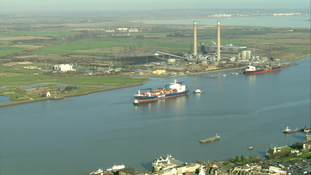 A large barge cruises down a river past an industrial plant . Available in HD.