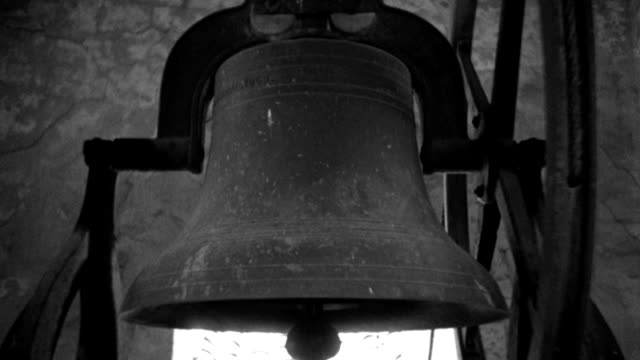 a large bell hangs motionless in a belfry as a hammer strikes its inner shell. - 1936 stock videos & royalty-free footage