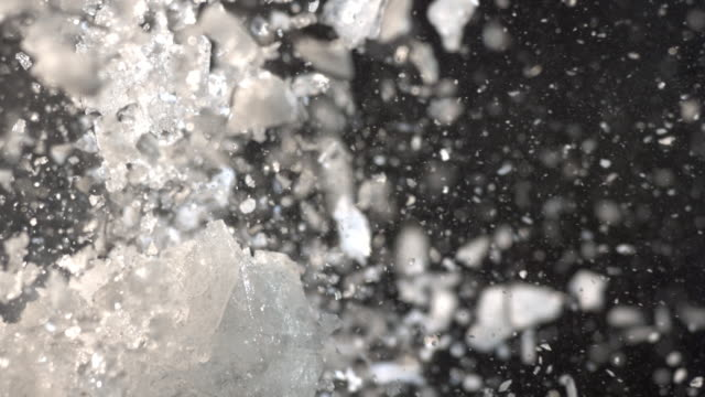 cu slo mo large block of ice exploding into tiny pieces / united kingdom - ghiacciato video stock e b–roll