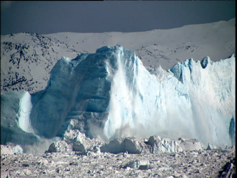 Large blue glaciers calving into sea Greenland